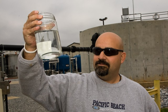 Charles Setters holds a jar of the Industrial Wastewater Treatment Plant's final product, clean water, which flows from the plant into Choccolocco Creek. Thanks to the plant, no chemicals or pollutants from the installation reach the creek.