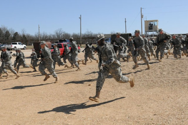 Soldiers from Co. C, 3-10th Inf. Bn., sprint toward storm shelters after receiving word of a possible tornado during the post severe weather drill, Tuesday.