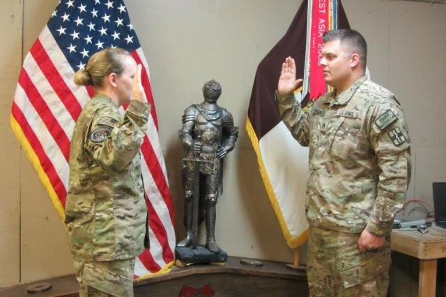 (From right to left) 1st Medical Brigade's Staff Sgt. Josh Abbatoye, an Acton, Calif. native, raised his right hand and recited the Oath of Enlistment administered by Capt. Alissa Byrne, battle captain for Task Force MED-Afghanistan, and made the ultimate commitment to the United States Army by re-enlisting indefinite. (U.S. Army Photo by Capt. Shubhra Jones)