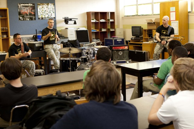 Sgt. 1st Class Thomas Lindsey, guitar, Staff Sgt. Glenn Robertson, drums, and Sgt. 1st Class Peter Krasulski, bass, host an education clinic for the students of Lafayette High School, March 14 in the school's band room.