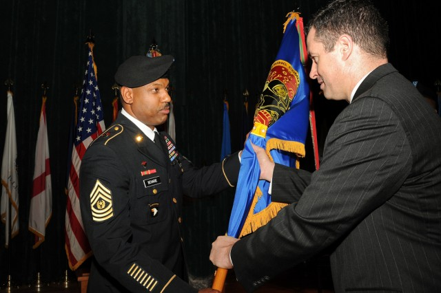 U.S. Army Research, Development and Engineering Command Director Dale Ormond, right, passes the RDECOM colors to incoming Command Sgt. Maj. Lebert Beharie during a Change of Responsibility ceremony at the Post Theater March 16 at Aberdeen Proving Ground, Md.