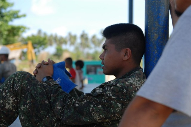 """PUERTO PRINCESA CITY, PALAWAN, Philippines """" Armed Forces of the Philippines Marine Pfc. Lionel Taladtad takes a moment to escape the mid-day heat, March 14, at the Tagbarungis Elementary School here. Taladtad is part of an AFP team working with the U.S. Army engineers, who are constructing an additional building at the school as part of the Engineering Civic Action Program of Balikatan 2012."""