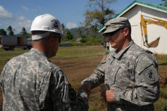 "PUERTO PRINCESA CITY, PALAWAN, Philippines "" U.S. Army Staff Sgt. Aaron Hall, right, civil affairs team sergeant, Civil Affairs Team-South, Combined Joint Civil Military Operations Task Force, shakes the hand of Sgt. 1st Class Michael Kendall, platoon sergeant, 643rd Engineer Company,84th Engineering Battalion on March 14.  Hall is conducting a civil affairs assessment of a school building project, in support of Balikatan 2012, an exercise focused on the Philippine-U.S. partnership and commitment to mutual defense and humanitarian assistance. Much of the labor, expertise and materials are locally sourced, while Armed Forces of the Philippines provides engineering support."