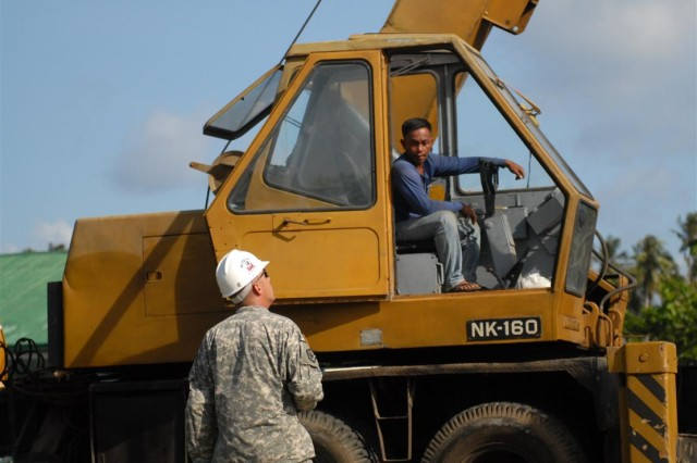 "PUERTO PRINCESA CITY, PALAWAN, Philippines "" U.S. Army Sgt. 1st Class Michael Kendall, platoon sergeant, 643rd Engineer Company, 84th Engineering Battalion directs a heavy equipment operator where to unload gear, March 14.  Kendall is assisting in a school building project, in support of Balikatan 2012, an exercise focused on the Philippine-U.S. partnership and commitment to mutual defense and humanitarian assistance. Much of the labor, expertise and materials are locally sourced, while Armed Forces of the Philippines provides engineering support."