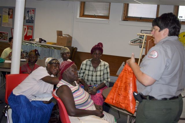 Lou Ann McCracken, a natural resources specialist with the U.S. Army Corps of Engineers Mississippi River Project, presents water safety information to local refugees, educating them on hidden dangers in the river.