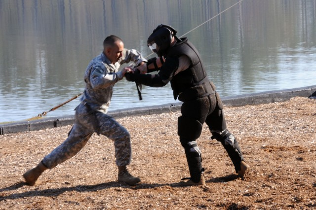 "A ""bad"" guy dressed in black tries to overtake a Ranger showing their exclusive fighting technique of Brazilian Jiu-Jitsu, known as a complete fighting system, during a demonstration provided by Soldiers of the Ranger Training Bridade at Fort Benning, Ga., March 15, 2012."