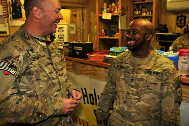 Chaplain (Maj.) Kent Walker, 25th Combat Aviation Brigade Chaplain, converses with Navy Petty Officer 3rd Class Alfred Williams, assigned to Provincial Reconstruction Team Farah from an Operational Health Support Unit in Ohio, after stopping in to relax at the First Cup at Mustang Ramp on Kandahar Airfield, Afghanistan, March 13.