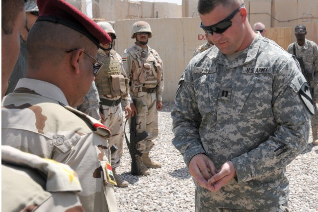 CONTINGENCY OPERATING BASE COBRA, Iraq -- Capt. Matthew Jung (right), commander, Troop B., 4th Squadron, 9th U.S. Cavalry Regiment, 1st Cavalry Division, U.S. Division-North, Iraq, prepares to hand over the keys to Iraqi officers from the 4th Battalion, 4th Brigade, 1st Iraqi army division, during the transfer of authority a checkpoint in Northern Diyala province June 30.  The TOA was part of the transition and closure of Contingency Operating Base Cobra in support of Operation New Dawn. The connexs contain equipment and supplies for the checkpoint.