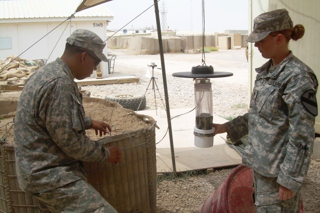 CONTINGENCY OPERATING BASE WARHORSE, Iraq -- Specialists Amanda Rose (right), a Flint, Mich., native, and Eddy Luengas, a Santa Anna, Calif., native, conduct a routine inspection on an insect trap at Teal Medical Clinic on Contingency Operating Base Warhorse, Iraq, July 29, 2011.  Rose and Luengas serve as preventive medicine specialists with 15th Brigade Support Battalion, 2nd Advise and Assist Brigade, 1st Cavalry Division, U.S. Division -- North, in support of Operation New Dawn.