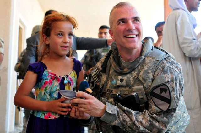 CONTINEGENCY OPERATING BASE WARHORSE, Iraq -- Lieutenant Colonel Nathan Cook, commander, 3rd Battalion, 82nd Field Artillery Regiment, 2nd Advise and Assist Brigade, 1st Cavalry Division, U.S. Division -- North, gives a toy to a young girl in the village of Yethrib, Iraq, Aug. 31, 2011, in celebration of Eid al-Fitr.