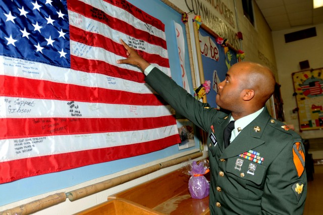 KILLEEN, Texas--Spc. Christopher Dotson, a native of Los Angeles, Calif., points to his signature on an American flag on display at Peebles Elementary School, Feb. 9, 2012.  The flag was signed by his unit while deployed and sent back to the elementary school as part of the Adopt-A-School program facilitated by Ft. Hood. Dotson, a Water Treatment Specialist assigned to A Company, 27th Brigade Support Battalion, 4th Brigade Combat Team, 1st Cavalry Division, joind other Soldiers at the school to help commemorate Black History Month.
