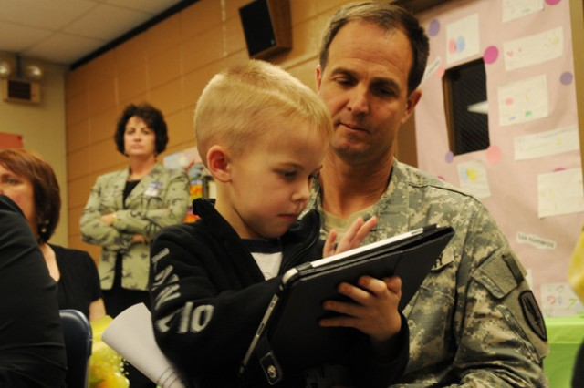 Col. Brian Bennett, 1st Avn. Bde. commander, watches as Parker, a kindergarten student, demonstrates what he can do on an iPad.