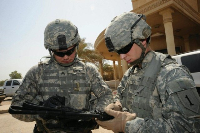 Sgt. Justin Green (left) and Pfc. Michael Moore (right) program a simple key loader to allow their radios to communicate securely between vehicles during a detail in Baghdad, Iraq, July 20, 2009.