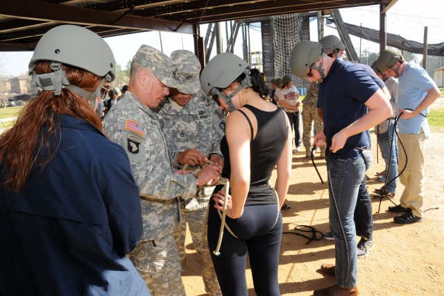 Nahmyo Thomas, a legislative correspondent with Rep. Jackie Speler of California's 12th District, gets help with her harness from Lt. Col. Kevin Butler, commander of the 2nd Battalion, 19th Infantry.