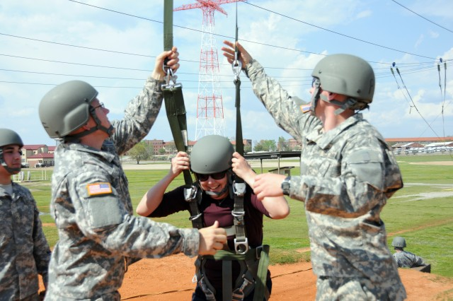 After landing, a congressional staffer is assisted with her harness by two Soldiers at Fort Benning, Ga.