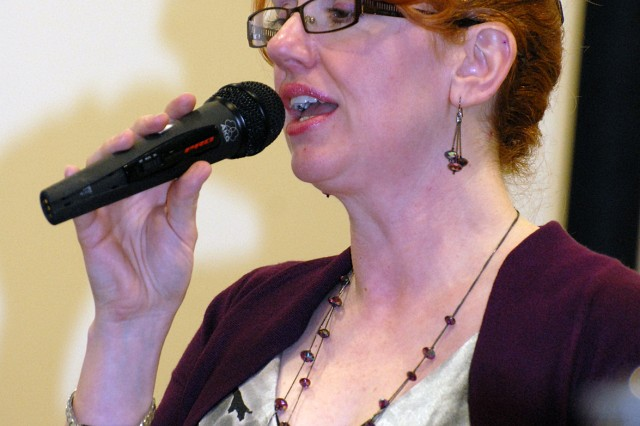 """Tisha Entwistle, Munson Army Health Center public affairs officer, sings the national anthem at the Women's History Month luncheon March 16 at the Frontier Conference Center. Entwistle also performed Jo Dee Messina's """"Bring On the Rain"""" at the event."""