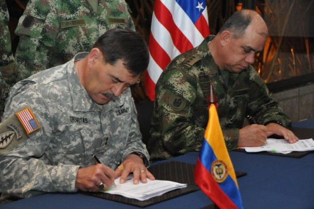 """BOGOTA, Colombia """" Maj. Gen. Simeon G. Trombitas, Army South commander, and Maj. Gen. Manuel Guzman, Colombian army deputy commander and chief of staff, sign the memorandum of understanding that will govern the agreed-to activities between the U.S. and Colombian armies for the next year.  The bi-lateral staff talks between the armies ended March 22.  (Photo by Andres Diaz, Colombian army)"""