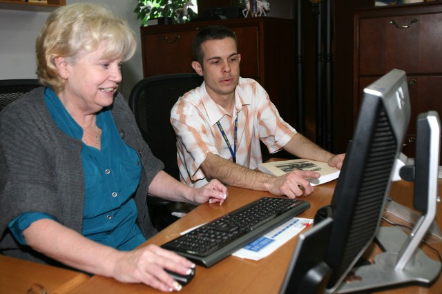 "Information technology specialist Kyle Conley (right) assists ""ace administrative asset"" Barbara Henry with a computer issue at the CW2 Christopher G. Nason Military Intelligence Library here."