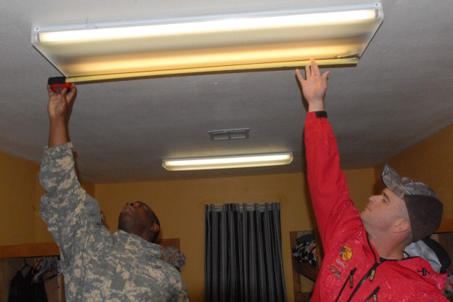 FORT HOOD, Texas--Sergeant 1st Class Mark Haliburton of Midway, Ala., and Sgt. 1st Class Daniel Schuman from Woodbridge, Va., both a member of the 2nd Brigade Combat Team Sergeant Audie Murphy Club, 1st Cavalry Division, measure a light to ensure they purchase the right size to replace a burnt out bulb at Central Texas Youth Services Option House in Killeen, Texas, March 10.