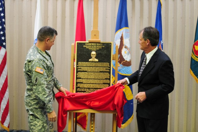 PRESIDIO OF MONTEREY, Calif. - Defense Language Institute Foreign Language Center Commandant Col. Daniel D. Pick and former-Dean of the Immersion Program Andrei Pashin unveil and dedicate a bronze plaque in the honor of Sgt. Cari Anne Gasiewicz. The plaque will be affixed to the immersion center building, renamed Gasiewicz Hall.