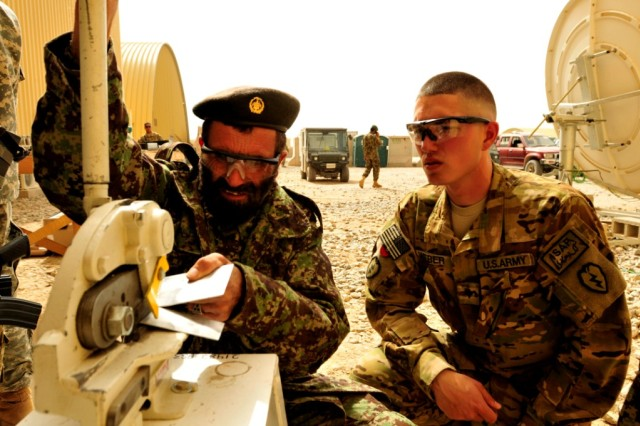 Capt. Saed Habib Rahman, Kandahar Air Wing, cuts out a patch with the press while Spc. Galen Weber, aircraft structural repairer with B Company, 209th Aviation Support Battalion, 25th Combat Aviation Brigade, looks on during sheet metal training on Kandahar Airfield, Afghanistan, March 19, 2012.