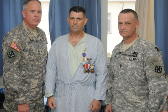Brig. Gen. David L. Weeks, commander of 411th Engineer Brigade, 412th Theater Engineer Command, and Command Sgt. Maj. Andrew Krom presented the Purple Heart and other awards to Warrant Officer Stephen Gilmore at Landstuhl Regional Medical Center in Germany, Mar. 21, 2012. Gilmore was wounded when his vehicle struck an Improvised Explosive Device less than two weeks prior in Afghanistan.