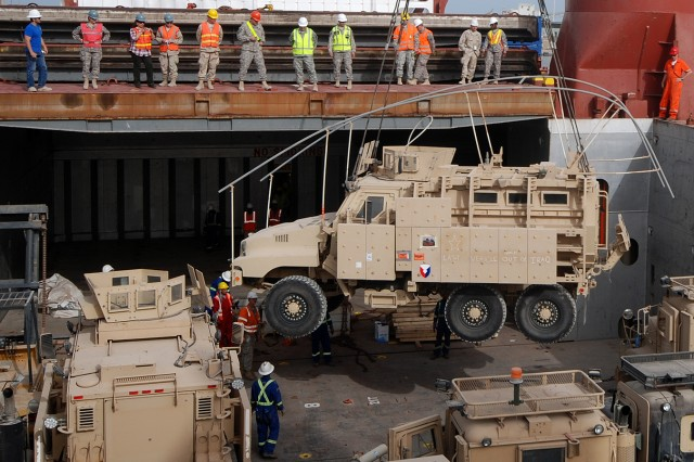 The last mine-resistant, ambush-protected vehicle to depart Iraq is lowered into the hold of the freighter Ocean Crescent at the Port of Ash Shuaiba, Kuwait, March 24, 2012, for transport to the United States. The Caiman Plus vehicle will be preserved and displayed at the 1st Cavalry Brigade Division Museum at Fort Hood, Texas.