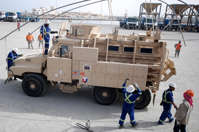 Workers prepare the last mine-resistant, ambush-protected vehicle to depart Iraq for loading aboard the freighter Ocean Crescent at the Port of Ash Shuaiba, Kuwait, March 24, 2012, for transport to the United States.  The Caiman Plus will be preserved and displayed at the 1st Cavalry Brigade Division Museum at Fort Hood, Texas.