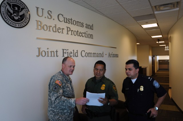 "Lt. Col. Stephen Goff, Southwest Regional Support Team lead planner, Joint Task Force-North, discusses a report Feb. 29, 2012, with Andy Adame, Border Patrol Special Operations Supervisor, and Chris Leon, Chief Customs and Border Protection Officer, at the Arizona Joint Field Command headquarters in Tucson, Ariz. From the Joint Field Command, leaders from JTF-N and the CBP coordinated ""Operation Nimbus II,"" a military support to federal law enforcement mission. Active-duty Soldiers from Fort Hood, Texas, and Fort Bliss, Texas, provided air and ground reconnaissance and surveillance support to the Border Patrol along the international borders in New Mexico and Arizona during the operation."