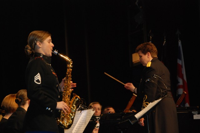 Sgt. Stacey Wilson, left, performs a saxophone solo while Lt. Col. Beth Steele, U.S. Army Europe Band and Chorus commander, conducts the band during the Hands Across the Sea concert earlier March 1-2 in Eppelheim and Oftersheim, Germany. Steele invited guest conductors and asked them to choose a musical selection that represents their nation's musical heritage.