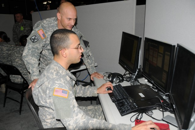 Capt. Benjamin Horner, left, observes as Spc. Jeremy Gomez plots points on a map using Command Post of the Future software during company CP training at the Brigade Modernization Command's Mission Command Center in preparation for the NIE 12.2
