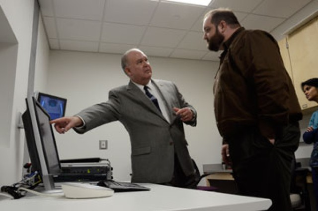 Undersecretary of the United States Army Joseph W. Westphal discusses MRI research and its application in the study of brain injury with Jeffrey Luci, assistant professor of neurobiology in the Imaging Research Center.