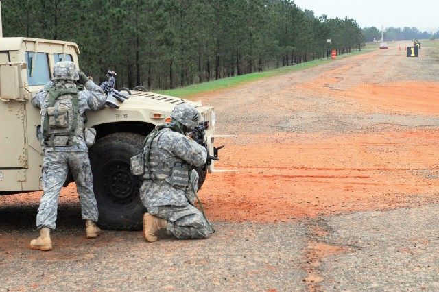 As a vehicle approaches (far right), Soldiers establish a traffic control point Friday as part of the Joint Non-Lethal Weapons Assessment at the McKenna Urban Operations Complex on Fort Benning. The Soldiers, all assigned to D Company, 3rd Battalion, 7th Infantry Regiment, out of Fort Stewart, Ga., employed a series of nonlethal devices during simulated runs to get the drivers to stop.