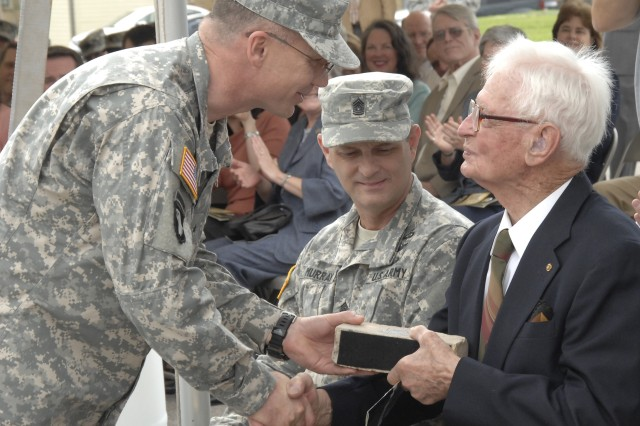 Brig. Gen. Stephen Leisenring presents retired Master Sgt. Givens Forsythe a brick symbolizing the men and women who have served in the Long Barracks since its construction in 1885 as part of the barracks ribbon-cutting ceremony March 27 at Fort Sam Houston, Texas. The brick was collected from the barracks during its $25 million renovation over the last two years. Leisenring is the former commander of the Mission and Installation Contracting Command, and Forsythe served in the Long Barracks in 1939.