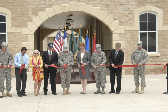 From left, Command Sgt. Maj. Rodney Rhoades, Mission and Installation Contracting Command, Danny Durobles, U.S. Army Corps of Engineers,  Joan Gaither, Society for the Preservation of Historic Fort Sam Houston, Retired Master Sgt. Givens Forsythe, Brig. Gen. Stephen Leisenring, former MICC commanding general, Dr. Carol Lowman, Army Contracting Command director, Brig. Gen. Theresa Carter, 502nd Air Base Wing commander, George Cabaniss, MICC deputy to the commanding general, and Command Sgt. Maj. John Murray, ACC, cut the ribbon officially opening the doors of the Long Barracks during a ceremony March 27 at Fort Sam Houston.