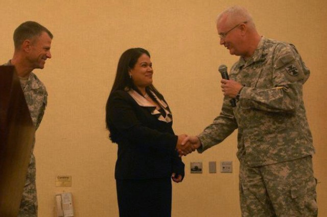 Brig. Gen. Douglas Satterfield, deputy commander of 412th Theater Engineer Command, congratulates Janette Chandler, Family Readiness Support Assistant for 841st Engineer Battalion, for an outstanding job in coordinating the unit's Yellow Ribbon event in Miami, Fla. (Photo: Capt. Maryjane Falefa Porter, 412th TEC Public Affairs)