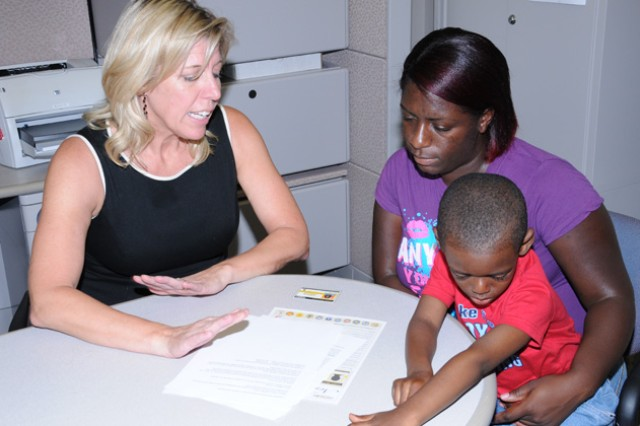 Survivor Outreach Services Financial Counselor Beth Gunter reviews benefits with survivor Fredda Jones and her son, Jamerius, in 2010. An Army Family Action Plan issue originating locally is now the Army's No. 1 issue to address through the program.