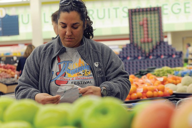 Peggy Santillan, military spouse, picks out fresh fruit March 13 shortly after the Fort Riley Commissary's ribbon-cutting ceremony.