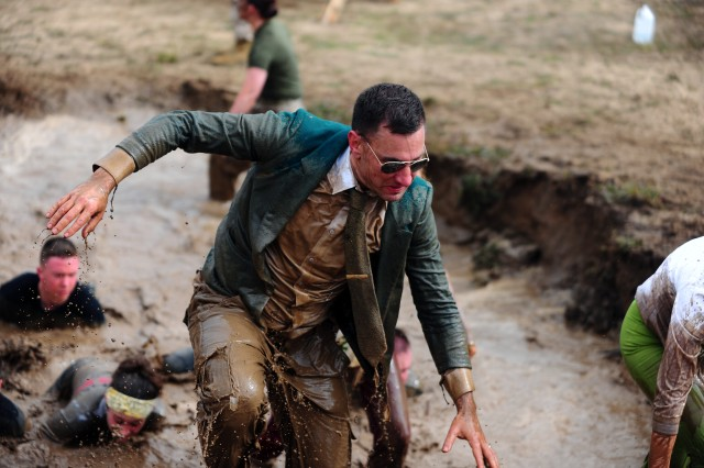 PRESIDIO OF MONTEREY, Calif. - A business-attired runner from Team Sabotage exits a mud pit manned by Marine Corps volunteers. Team Sabotage was one of 33 5-person teams comprised of military service members that competed in the race. In total, more than 3,000 racers participated this year in the individual and team divisions.