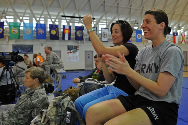 From left, Spc. Elizabeth Wasil and Staff Sgt. Stefanie Mason cheer on friends competing in sitting volleyball clinics earlier this month at Fort Meade, Md.