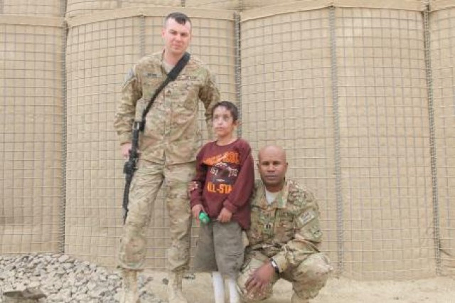 Sgt. Anthony Merino, senior medic for Bravo Company, Task Force 3-66, 172nd Infantry Brigade, and Capt. Giles Wright, commander for Bravo Co., TF 3-66, 172nd Inf. Brig., pose for a picture on Combat Outpost Kushamond, Paktika province, Afghanistan, with Matten, an 8-year-old Afghan boy whose face was severely damaged and blinded by an improvised explosive device. Merino saved Matten's life and he is now being cared for by officials of the Government of the Islamic Republic of Afghanistan.
