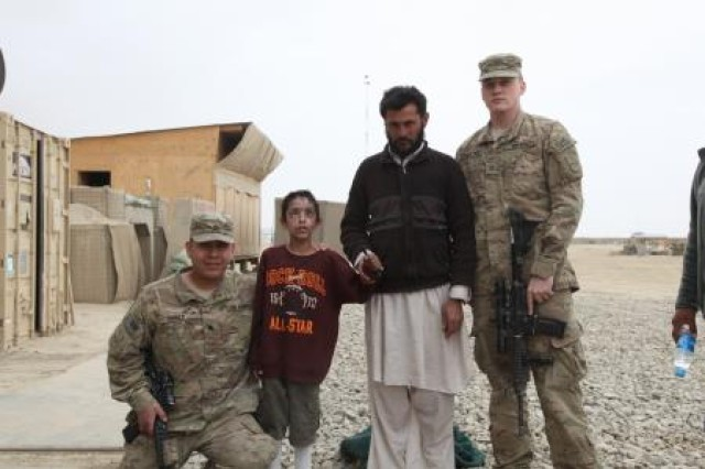 Sgt. Michael Torres, rifle section leader, Bravo Company, Task Force 3-66; Sultan, a villager from Kushamond district, Paktika province; and Pfc. Cody Sandstrom, Company B, TF 3-66; stand with Matten, an 8-year-old boy who was blinded and whose face was severely damaged by an improvised explosive device, March 14, 2012. The group escorted him to the Craig Joint-Theater Hospital at Bagram Air Field, where they remained with him for 10 days until his release. Matten is now being cared for by Sultan and officials of the Government of the Islamic Republic of Afghanistan.