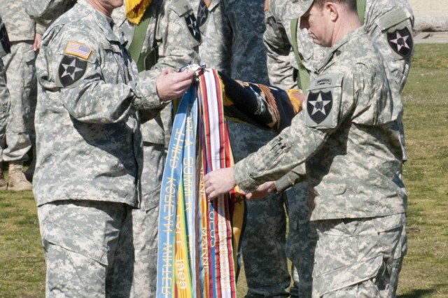 JOINT BASE LEWIS-MCCHORD, Wash. -- Lieutenant Col. Gregory Harkins (right), commander, 4th Battalion, 23rd Infantry Regiment and Command Sgt. Maj. Paul Biggs (left), senior enlisted leader, 4-23 Inf., hang a Navy Presidential Unit Citation streamer on the battalion colors March 23. According to the citation, the Navy Presidential Unit Citation was awarded to each company in 4-23 Inf. Regiment, and Alpha Company, 1st Battalion, 17th Infantry Regiment, for their extraordinary heroism in action against an armed enemy while participating in operation Moshtarak, with the Marine Expeditionary Brigade in the Marjah district, Afghanistan in February, 2010.