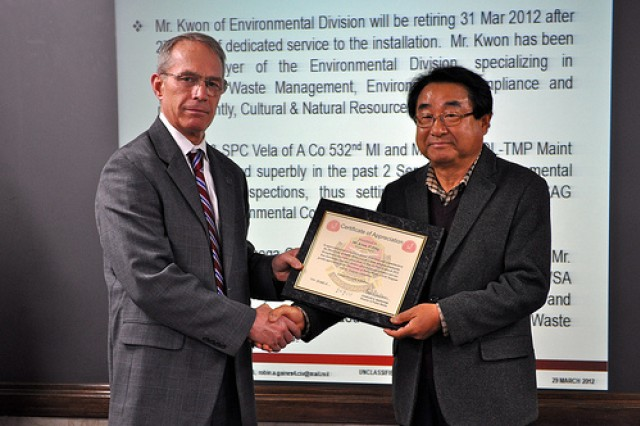U.S. Army Garrison Yongsan Deputy Commander Henry Stuart presents DPW Environmental Protection Specialist Kwon O-pong with a certificate of appreciation for his 27 years of dedicated service to the Garrison during the Environmental Quality Control Committee meeting March 29.