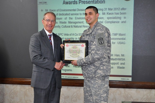 U.S. Army Garrison Yongsan Deputy Commander Henry Stuart presents Spc. Matthew Vela, Alpha Company 532nd Military Intelligence Battalion, with a certificate of appreciation for his superb performance as his unit's Environmental Officer during the Environmental Quality Control Committee meeting March 29.