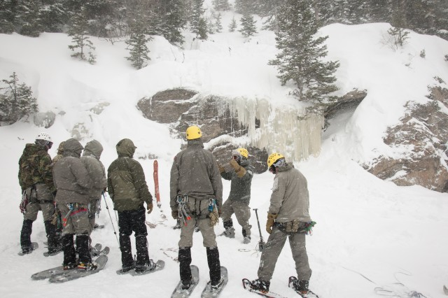 A Special Forces Advanced Mountain Operations School instructor (second from right) addresses his group of students before demonstrating ice-climbing and rope techniques on the cliff behind him.