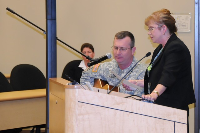 "Chaplain (Maj) Ken Hubbs and Ms. Laura Steele of the 81st Regional Support Command sing an original composition during Women's History Month celebration on March 28. The song, entitled ""Eyes Wide Open"" was written by Ch. Hubbs and well-received by the audience."