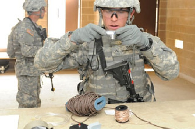Pvt. Cody Adams dusts for fingerprints, while Spc. David Ruiz takes notes on items at the site. Both Soldiers are from Company E, 701st Military Police Battalion.