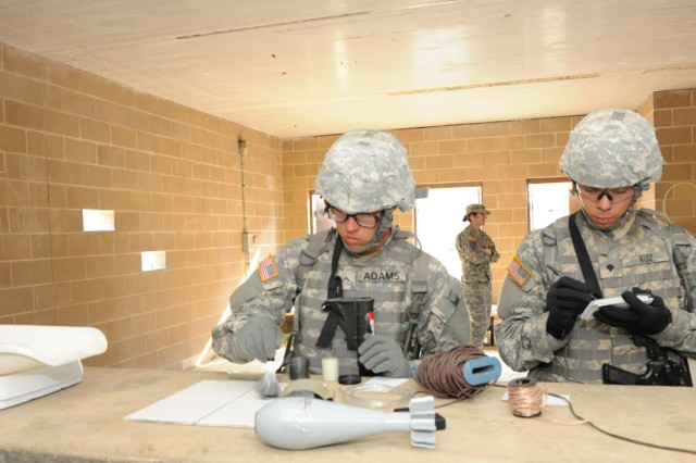 Pvt. Thomas Bennett, Company E, 701st Military Police Battalion, photographs evidence during site exploration training.
