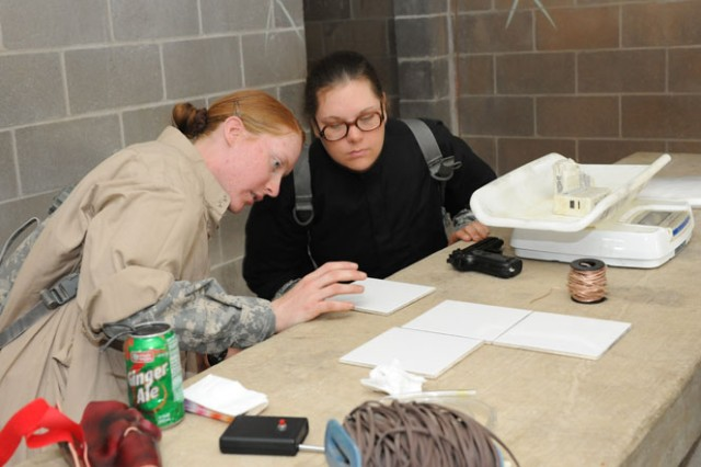 Pfc. Judith Pruett, in black, watches Pvt. Annette Galvin place her fingerprints on tiles as part of the training for fellow Company E, 701st Military Police Battalion Soldiers.